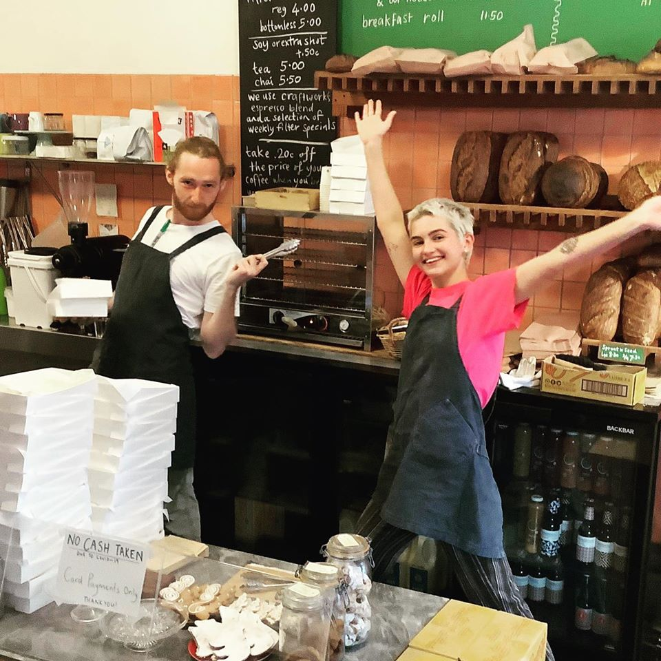 2 staff members standing in the serving area hands stretched out before products